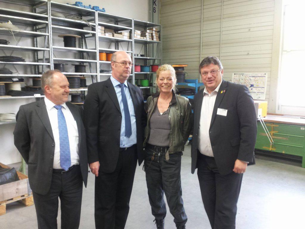 Andreas Rimkus mit Geschäftsleitung sowie der Betriebsratsvorsitzenden von Vossloh Kiepe während des Rundgangs durch die Fertigungshalle